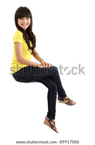 Pretty girl sitting casual on big blank billboard poster sign with lot of copy space.isolated on white background