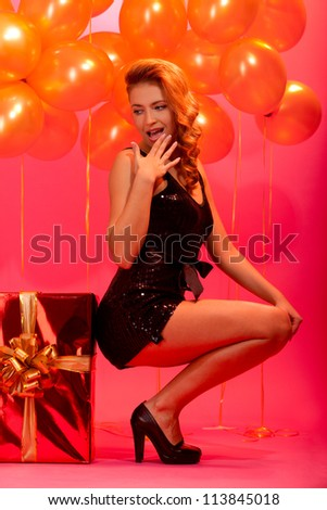 pretty girl sitting near the big gift box guessing gift against balloons and pink background