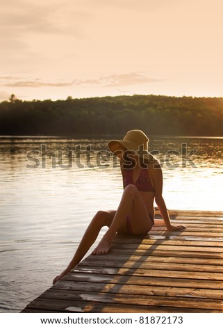 pretty girl sitting on a dock looking into the lake at sunset