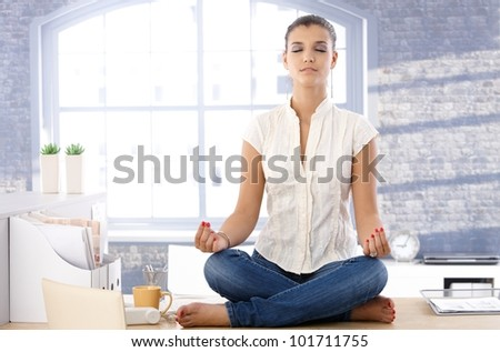 Pretty girl sitting on top of desk in bright office, meditating.