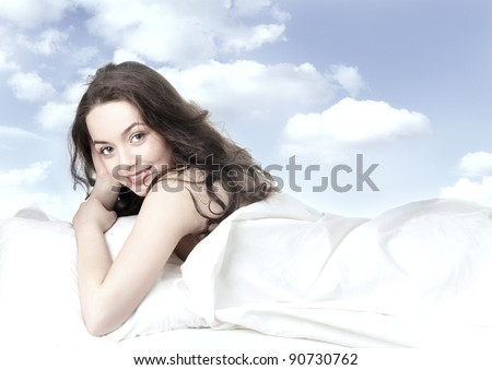 pretty girl sleeping on the white linen on background of clouds