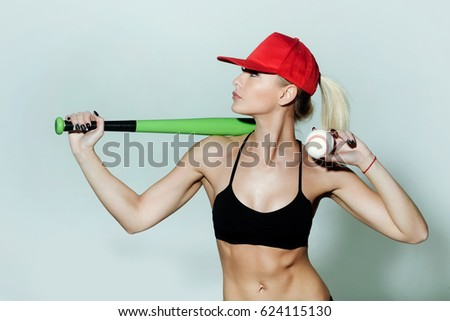 Pretty girl, sporty woman player, fit athlete, with sexy, muscular body, torso, hold green baseball bat, ball in black sportswear bra and red cap on grey background. sport and healthy lifestyle #624115130