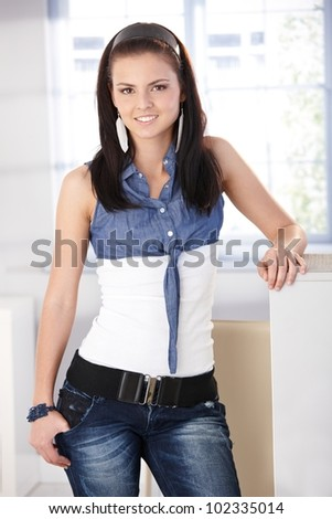 Pretty girl standing at home in jeans and blouse, smiling, looking at camera.