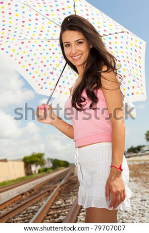 Pretty girl standing by a railroad track holding a colorful white polka dot umbrella.