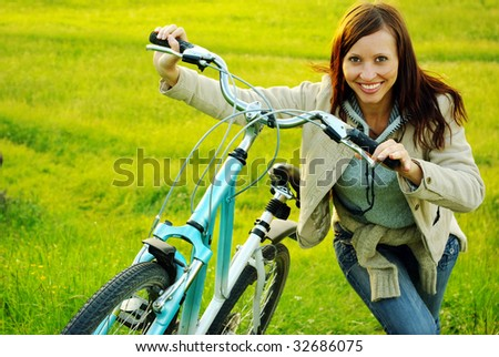 Pretty girl standing with a bicycle.