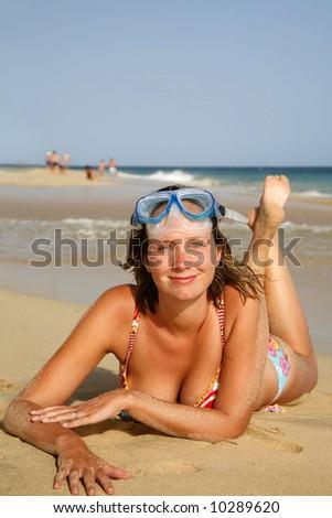 Pretty girl sunbathing on golden beach - stock photo