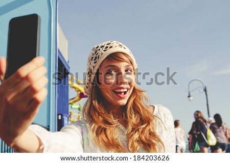 "Pretty girl taking a ""selfie."" - stock photo"