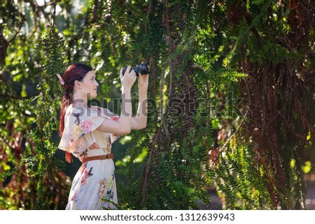 Pretty girl taking photos in a sunlit garden with her digital camera