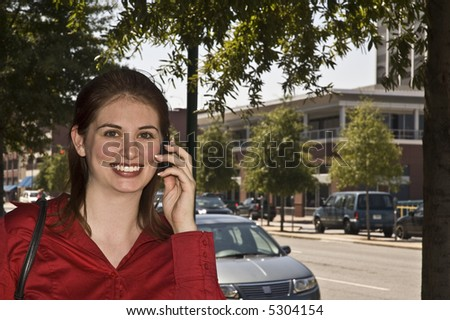 Pretty girl talks on the cell phone as she walks down the street.