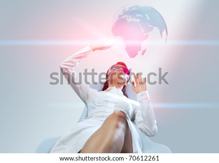Pretty girl wearing 3d anaglyph stereo glasses. Operating futuristic 3d interface. Touching three-dimensional globe. One of a series.