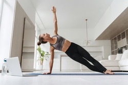 Pretty girl wearing leggings and short top standing in side plank on one hand at home, training body core and balance, strengthening muscles. Attractive female practicing yoga in her room with laptop
