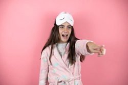 Pretty girl wearing pajamas and sleep mask over pink background pointing with finger surprised ahead, open mouth amazed expression, something on the front