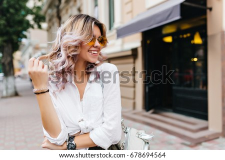 Pretty girl wearing sunglasses and bracelets playing with her short curly hair and smiling on the street. Outdoor portrait of laughing blonde young woman in white shirt standing near store. #678694564