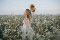 Pretty girl with a hat in her hand walks in a field with field flowers and smiles sincerely