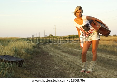 Pretty girl with a suitcase on a countryside road