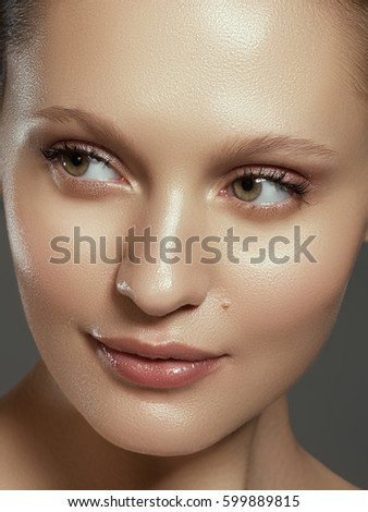 Pretty girl with big eyes and dark eyebrows smiling, a model with light nude make-up, gray studio background, beauty photo, close up. Beautiful spa model girl with perfect fresh clean skin