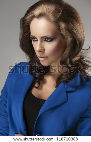 pretty girl with blue jacket and fluffy hair, she is turned of three quarters at right