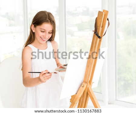 Pretty girl with brush in hand. Creative teen girl paitning a picture on easel. Girl practising drawing in art school