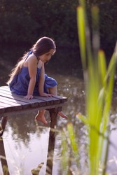 pretty girl with dark long hairs is sitting on the weathered wooden bridge near the countryside pond and looking curiously in the water, summer time and playing