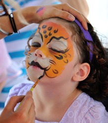 Pretty girl with face painting of a jaguar
