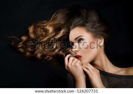 pretty girl with flowing hair and red lipstick turned at right with hand near the chin