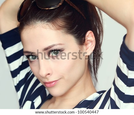 Pretty girl  with green eyes and hands behind the head. With sunglasses on the head and summer bright dress looking happy
