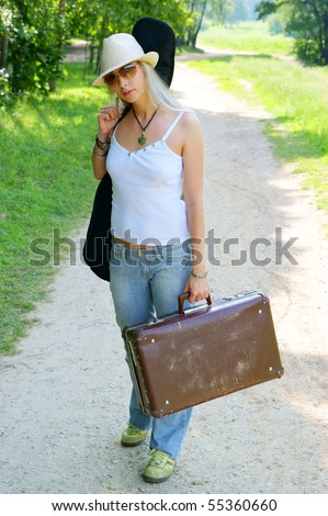 Pretty girl with guitar and baggage on the road