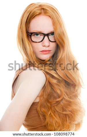 Pretty girl with long red hair wearing brown shirt and vintage glasses. Fashion studio shot isolated on white background. - stock photo