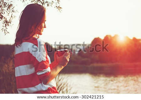 pretty girl with morning coffee at river sunrise