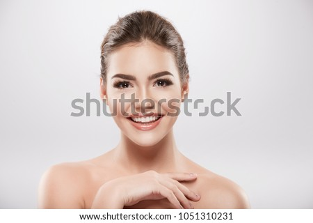 Pretty girl with nude make up and naked shoulders posing at grey background, beauty photo concept, skin care, hydrated skin, smiling.