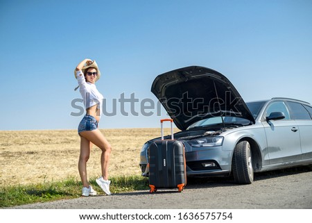 Pretty girl with suitcase standing near car and wiat for her dreaming trip Zdjęcia stock ©