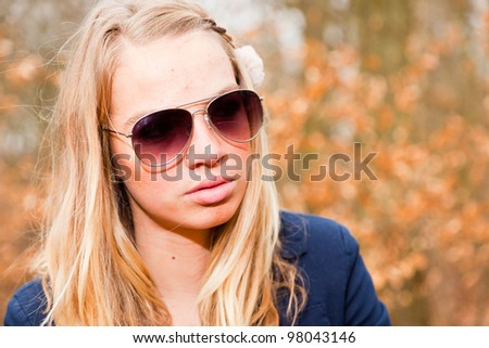 Pretty girl with sunglasses in autumn forest. Fashion style photo.