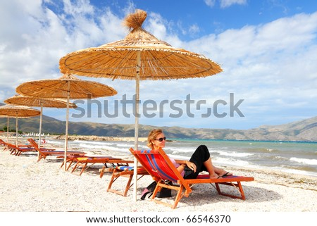 pretty girl with sunglasses  lying on a beach couch under a straw parasol enjoys a quiet summer day on the adriatic coast of Albania