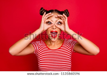 Pretty girl with surprised face holding fingers near eyes like glasses: mask like super hero or owl isolated on red background #1135860596
