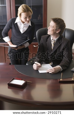 Pretty girl with the folder in her hands and man sitting at the table and signing the document