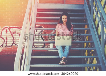 Pretty girl working with laptop sitting on stairs of stairway stock photo