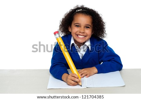 Pretty girl writing in her notebook and flashing smile by grinding her teeth.