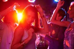 Pretty girls dancing in night club on background of guys