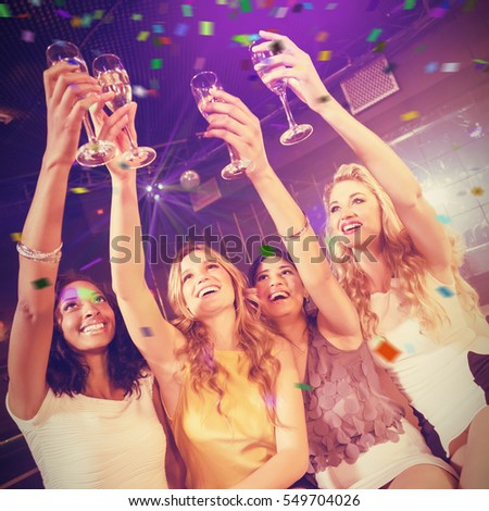 Pretty girls holding champagne glass against flying colours