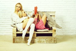 Pretty girls or two sexy cute women with blond hair in home wear read book on wooden pallet sofa on white brick wall