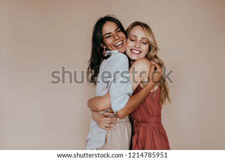 Pretty girls with trendy makeup embracing on light background. Excited caucasian sisters expressing love.