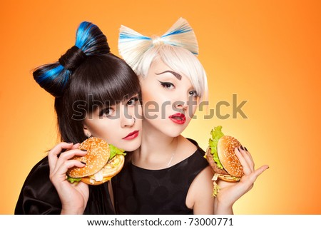 pretty girls with unhealthy burgers isolated in studio