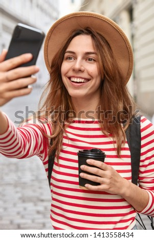 Pretty glad traveler clicks selfie photo, makes new pictures, uses cell phone and application, enjoys leisure outdoors, drinks aromatic coffee from disposable cup, wears headgear and striped jumper.