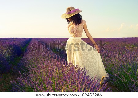 Pretty glamorous lady standing in a field of lavender flowers - stock photo
