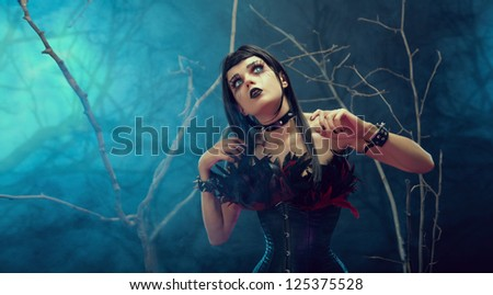 Pretty gothic girl wearing tight feather corset, studio shot with fog and branches
