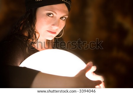 Pretty gypsy woman protectively holding her arms around her crystal ball