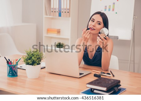 Pretty happy businesswoman doing make up in office Сток-фото ©