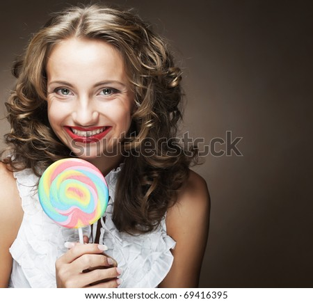 pretty happy curly  girl with a lollipop in her hand