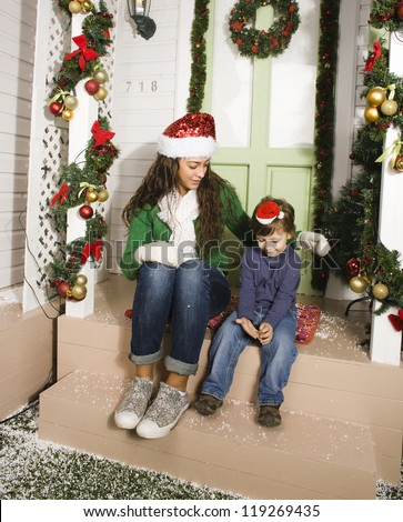 pretty happy family sitting in front of door decorated on Christmas