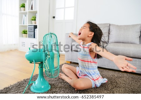 pretty happy female kid opening arms enjoying cool wind from electric fan and sitting on floor in living room at summer vacation. #652385497